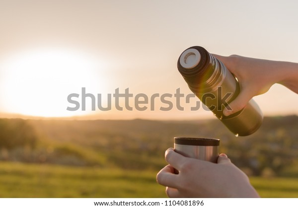 Close-up view of the female's hand holding thermal flask and filling the cup with tea. Concept of the lunch in journey, traveling, journey, hiking, backpacking.