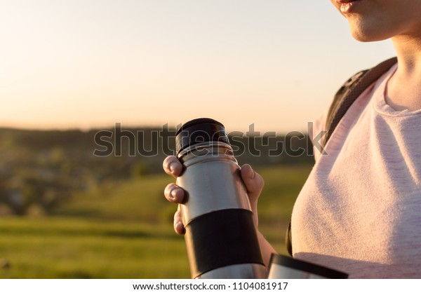 Close-up view of the female's hand holding thermal flask on the sunset. Concept of the lunch in journey, traveling, journey, hiking, backpacking.