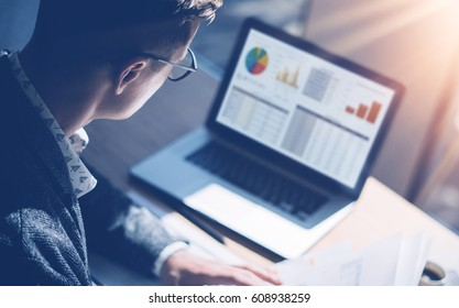 Closeup view of finance market analyst in eyeglasses working at sunny office on laptop while sitting at wooden table.Businessman analyze stock report on notebook screen.Blurred background,horizontal