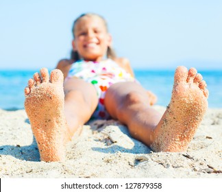 Close-up view of foots by the girl lying on the sand beach.