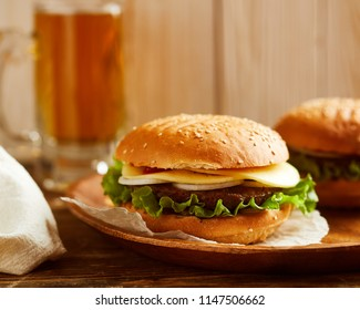 Close-up view of fresh burger, served on wooden plate. Glass of beer on background