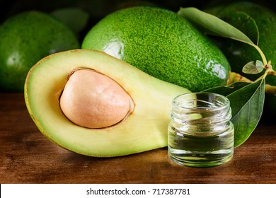 Closeup view of fresh green avocado and natural avocado oil on wooden table. Healthy eco product of organic farming. Skin, body and hair care. Handmade cosmetic. Home spa.