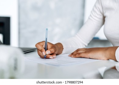 Close-up view, gentle, female hands signing documents in bright office