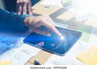 Closeup view of girl touching the screen of digital tablet with your finger on workplace.Concept business people working with mobile gadgets.Visual effect,flares,blurred background. Horizontal