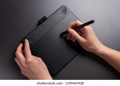 Closeup view of girl's hands draw on surface of graphic tablet. Designer work with graphic tablet