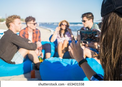 Closeup view of Girlshooting photo of group of friends on the beach. They have party and drinking alcohol . Happy youth time. Focus on smartphone