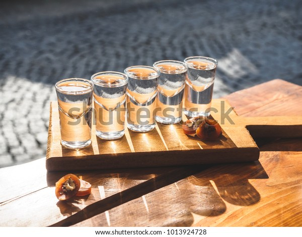 close-up view of glasses with chacha and delicious traditional sliced churchkhela on wooden table