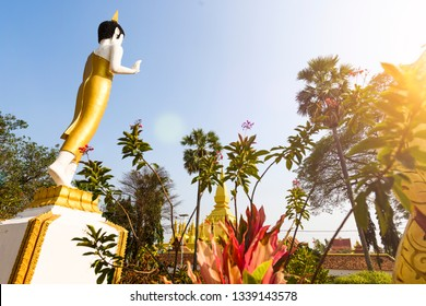 Close-up view of a gold colored Buddha statue facing the beautiful Great Stupa (Pha That Luang) in Vientiane. Pha That Luang is a gold-covered large Buddhist stupa in Vientiane, Laos.