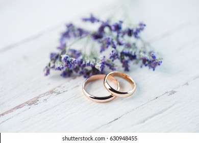 Close-up view of golden wedding rings and beautiful small blue flowers on wooden tabletop