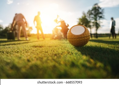 Close-up view of golf ball on grass and silhouettes of golfers playing behind