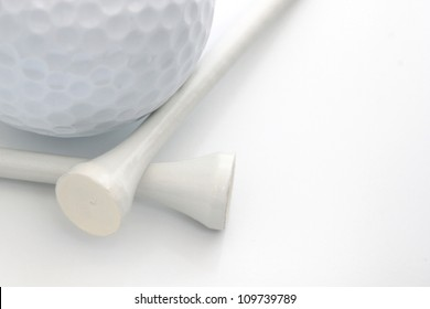 Closeup view of a golf ball with white tees over white