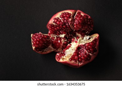 Closeup view of grain red grenades. Juicy ripe red pomegranates or pomegranates. Fruits of red ripe pomegranate on a studio background. Vegetarian concept, organic vitamins. Organic and healthy pomegr
