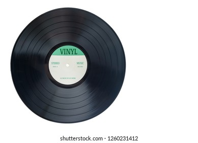 Closeup view of gramophone vinyl LP record or phonograph record with green label. Black musical long play album disc 12 inch 33 rpm spiral groove. Stereo sound record. Isolated on white background.