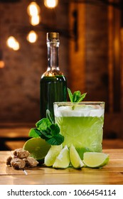 close-up view of green van gogh cocktail in glass with bottle of absinthe on wooden table