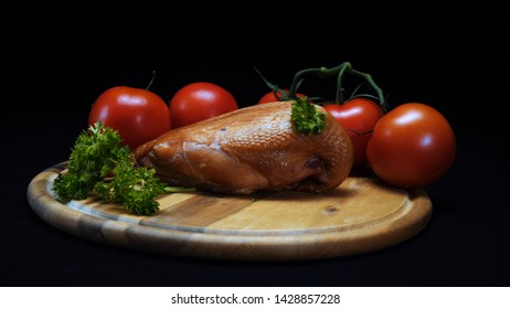 Close-up view of grilled chicken, tomatoes and greens lying on a wooden board on the black background. Frame. Ingredients for cooking
