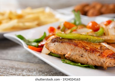 A closeup view of a grilled salmon steak, in a restaurant or kitchen setting.