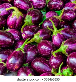 Close-up view group of fresh organic raw ripe Eggplant (or Brinjal) on display at Vegetable Stall of Local Market at Little India, Sinagpore. Colourful vegetable background and healthy concept