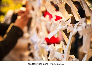 Close-up view Group of Omikuji, a fortune telling paper strip, tied on the ropes with blurred background. People believe that leaving bad luck omen omikujis behind, it will turn to good luck instead.