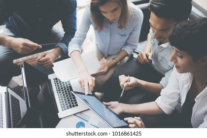Closeup view of group young coworkers working on mobile laptop computer at office.Woman holding tablet and pointing on touch screen. Horizontal, blurred background