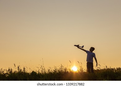 Closeup view of hand of happy caucasian child boy playing with toy airplane outside in meadow on sunny sunset time. Dream, imagination, curiosity concept. Horizontal color photography.