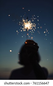 Close-up view of hand holding burning sparkler in evening darkness.