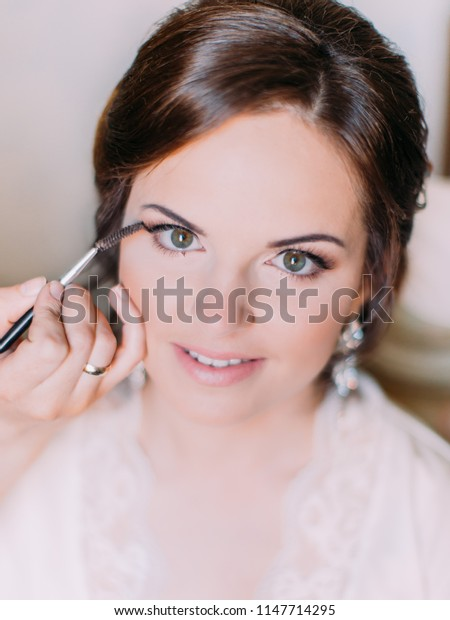 Close-up view of the hand of the makeup artist doing the makeup for the bride.