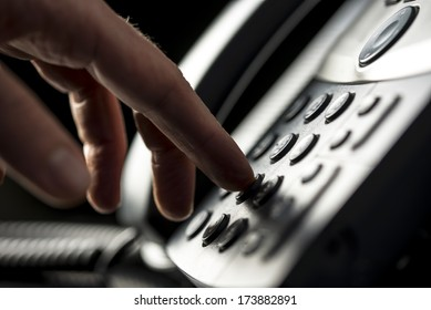 Closeup view of the hand of a man making a telephone call on a desktop instrument pressing the numbers on the keypad
