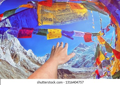 Closeup view of hand  on the top of  mount  Everest .View of Mount Everest and Nuptse  with buddhist prayer flags from kala patthar in Sagarmatha National Park in the Nepal Himalaya