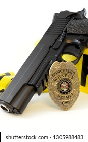 Closeup view of a handgun with a weapons badge and some police tape for law enforcement.