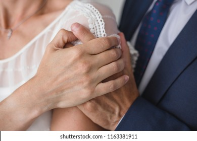 Closeup view of hands of bride and groom. Horizontal color image.