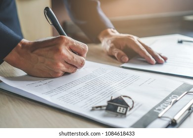 close-up view hands of businessman signing leasing home documents and have a apartment keys on paperwork.