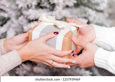 Closeup view of hands with gift box. Giving and receiving present on Christmas event. Love and romance couple celebrate xmas or New year holiday. X-mas fir tree on background.