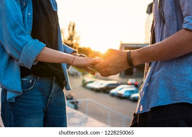 Closeup view of hands of lovely young couple dating during summer sunset. they wear jeans clothes. modern youth relationship