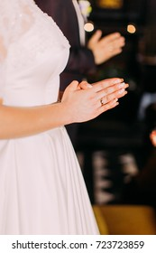 The close-up view of the hands of the praying bride.