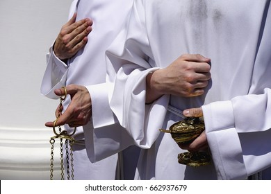 Close-up view of hands of two priest's assistants in white clothes and with a censers in his hands. Greek Catholic holiday of Body and Blood of Christ, Kiev, Ukraine. Right hands is pressed to body