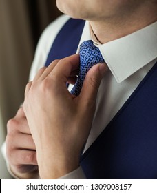 Closeup view of handsome man getting ready to formal event. Man dressing up white shirt, blue waistcoat and necktie. Color photography.