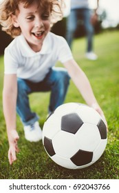 close-up view of happy little boy playing with soccer ball at park