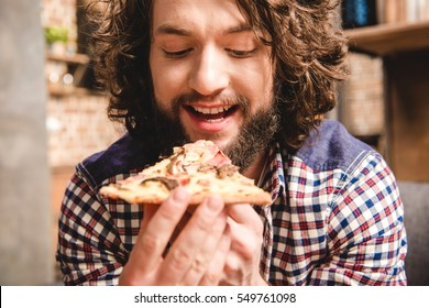 Close-up view of happy man eating pizza