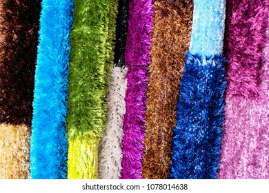 A close-up view of a heap of decorative carpets with fringes