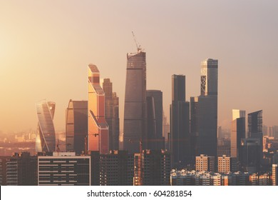 Close-up view from high point of futuristic modern contemporary skyscrapers and business area under construction of metropolitan on early hazy morning with cranes in foreground, Moscow city, Russia
