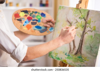 Close-up view of highly gifted painter while he is painting his picture.
