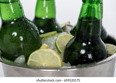 Close-up view of ice cubes, lemon slices and green beer bottles in bucket isolated on white