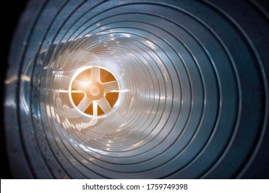 closeup view from inside the galvanized steel air duct on the exhaust fan in the background light, the front and back background is blurred with a bokeh effect