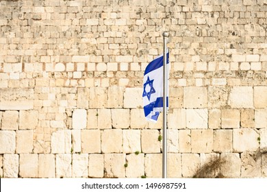 Close-up view of the Israeli Flag waving in front of the Western Wall (Wailing Wall) in Jerusalem, Israel. The Flag of Israel can be seen all around the country, and is a symbol of joy and dreams.