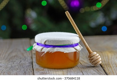 Close-up view of jar of honey decorated color ribbon with wooden honey dipper on wooden background