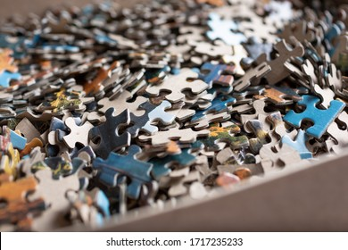 A closeup view of a jigsaw puzzle box and its many pieces.