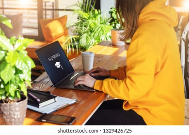 Close-up view of laptop screen with inscription e-learning. Sunny day. Girl in yellow hoodie sits in cafe at table,works on computer. Student doing homework. Business online education for adult.