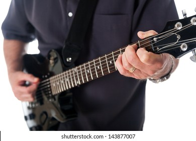 Close-up view of the left hand of a man fingering a chord on the fingerboard of an electric guitar.