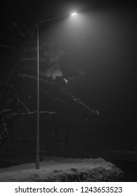 Closeup view of the light tower on empty winter asphalt road, which illuminated by dot lamp with roadside covered by snow in the Misterious dark night.