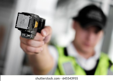 Closeup view of a loaded stun gun in a hand of a young man wearing high visibility vest